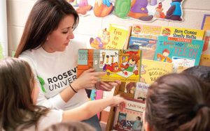 Teacher wearing a Roosevelt University shirt while reading to children in a classroom